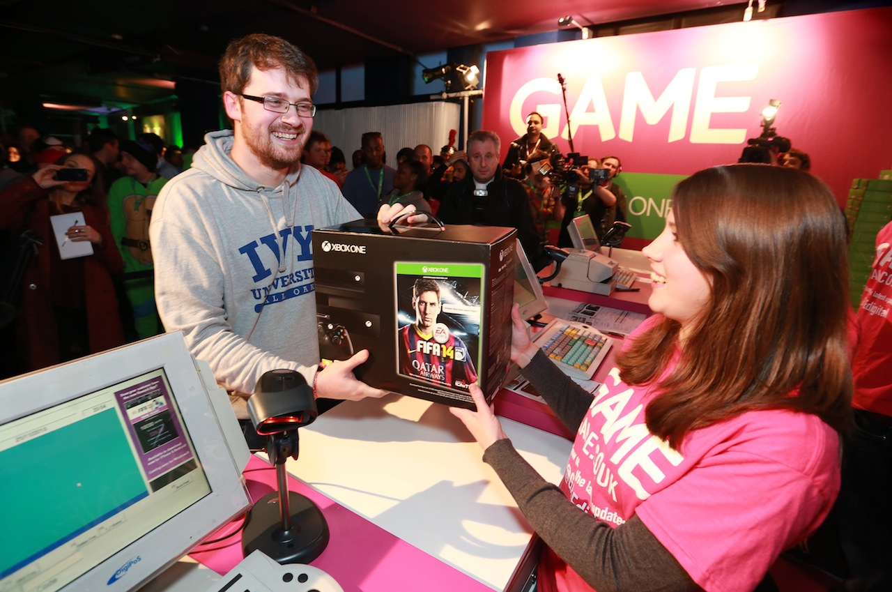 EDITORIAL USE ONLY Charlie Pulbrook from Sidcup is first person to pick up an Xbox One served by Mary Antieul from GAME after the midnight release of the console at the pop-up GAME store at Trocadero in London's Leicester Square. PRESS ASSOCIATION Picture date: Thursday November 21, 2013 Photo credit should read: Matt Alexander/PA Wire